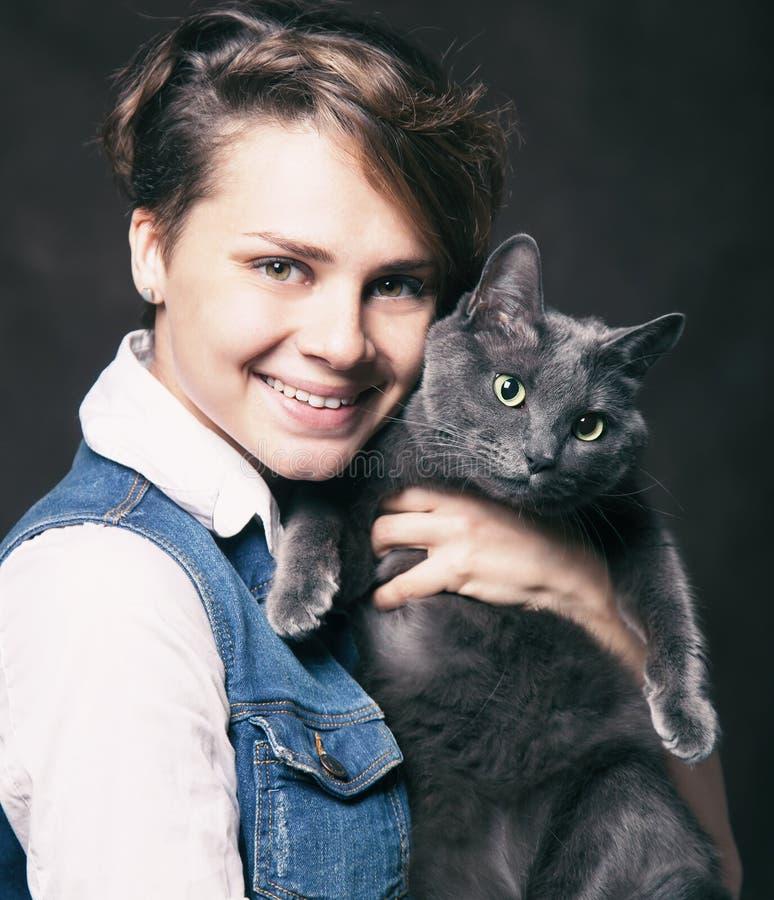 Jovem mulher bonita com o gato azul do russo Amor para o animal de estimação Studi fotografia de stock royalty free