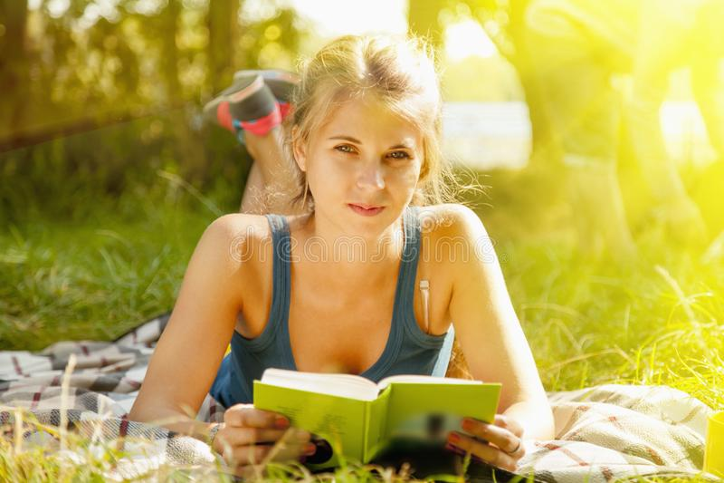 Jovem mulher bonita com o livro na grama resto, conhecimento, fotografia de stock