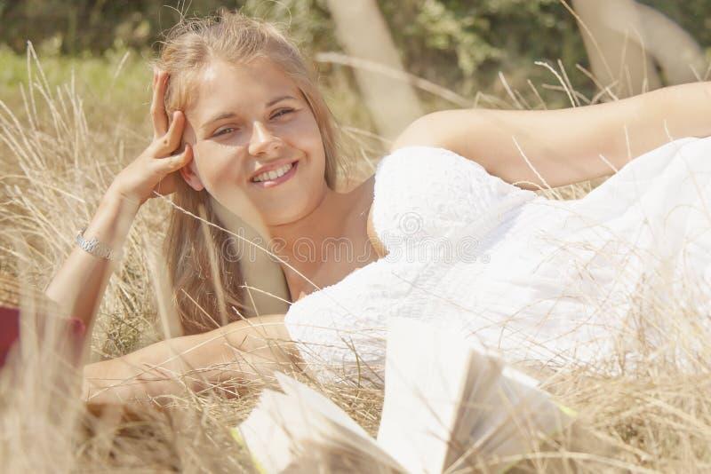 Jovem mulher bonita com o livro na grama fotos de stock royalty free