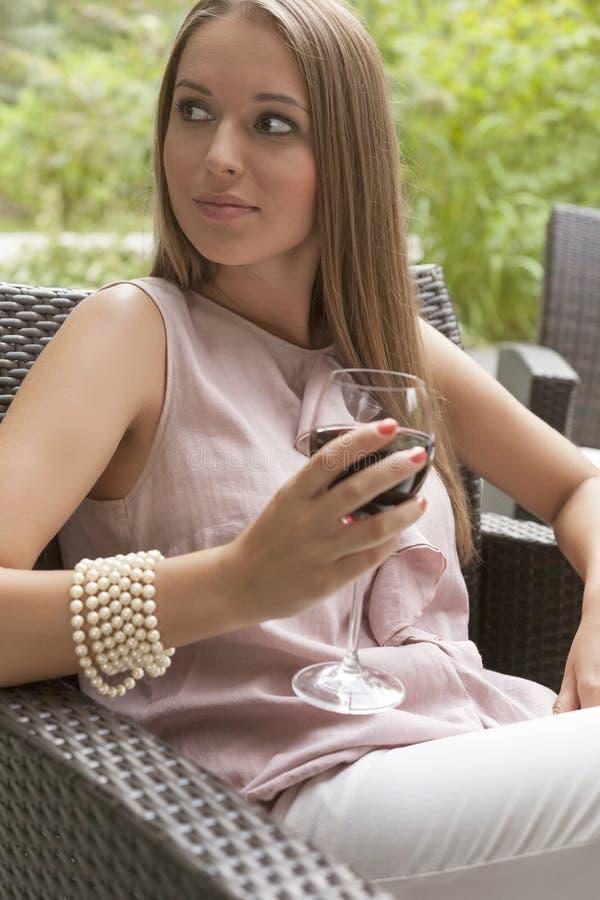 Jovem mulher bonita com o vidro do vinho tinto que senta-se na cadeira fora fotografia de stock