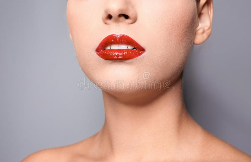 Jovem mulher bonita com os bordos lustrosos vermelhos no fundo cinzento fotos de stock