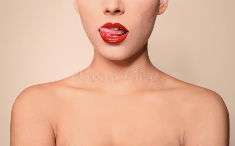 Jovem mulher bonita com os bordos lustrosos vermelhos no fundo da cor fotos de stock