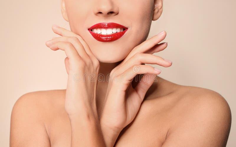 Jovem mulher bonita com os bordos lustrosos vermelhos no fundo da cor imagem de stock royalty free