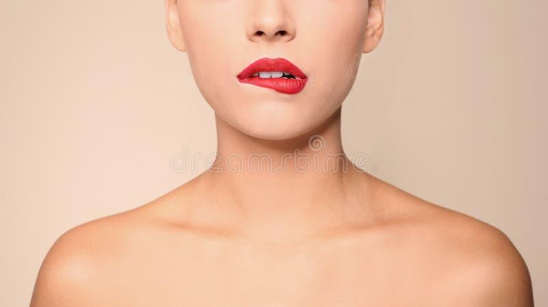 Jovem mulher bonita com os bordos vermelhos no fundo da cor fotografia de stock royalty free