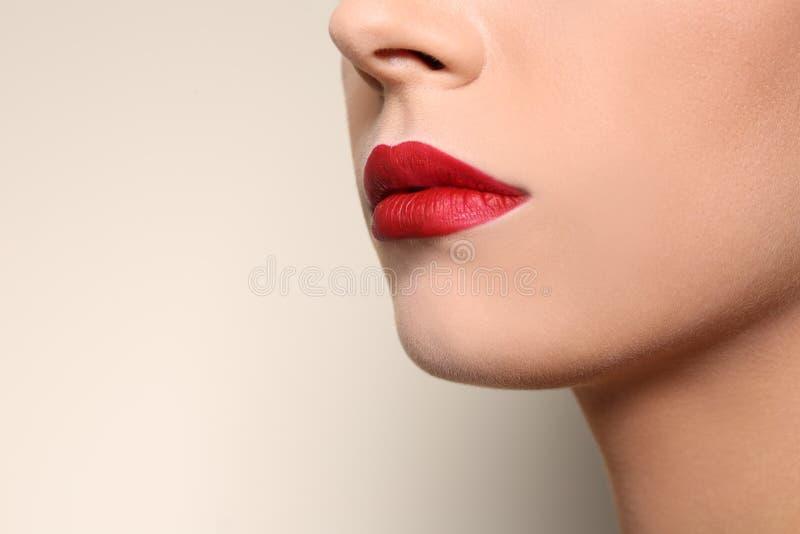 Jovem mulher bonita com os bordos vermelhos no fundo da cor, close up fotos de stock