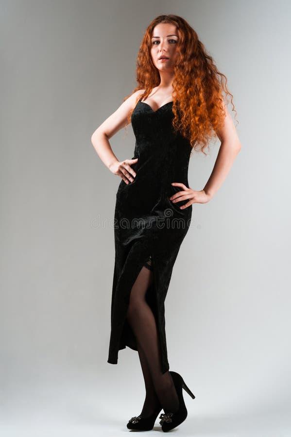 Jovem mulher bonita com os cabelos vermelhos que estão no fundo cinzento imagens de stock