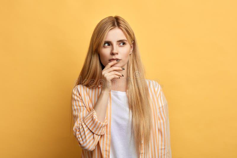 A jovem mulher bonita com os dedos em seus bordos expressa emoção confusa fotos de stock