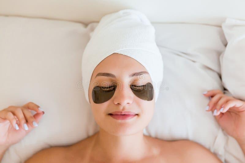 Jovem mulher bonita com os remendos inferiores do olho no roupão que encontra-se na cama Menina feliz que toma dsi mesma Skincare imagem de stock