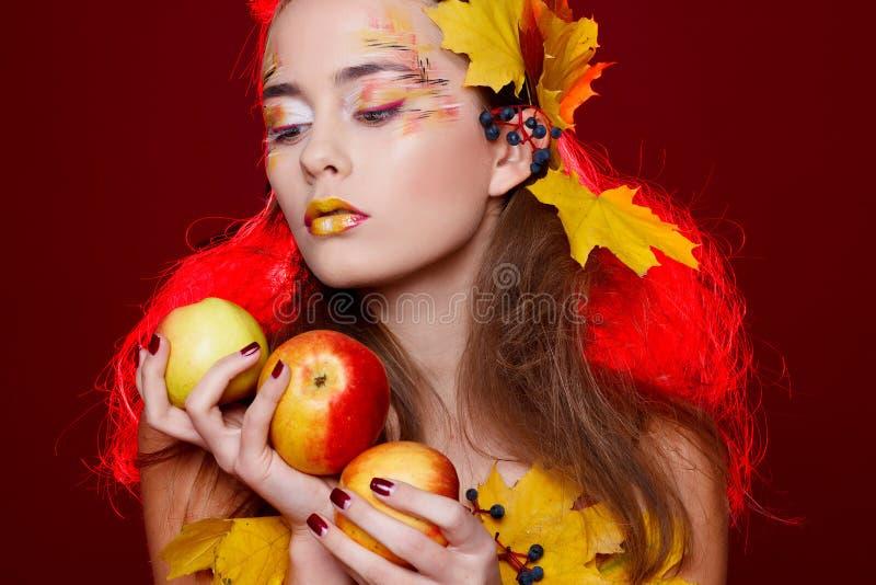 A jovem mulher bonita com outono compõe guardar maçãs nela fotos de stock royalty free