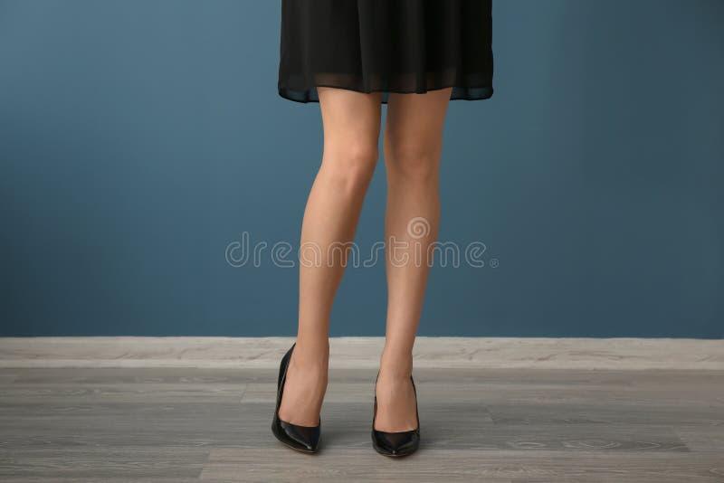 Jovem mulher bonita com pés longos contra a parede da cor foto de stock