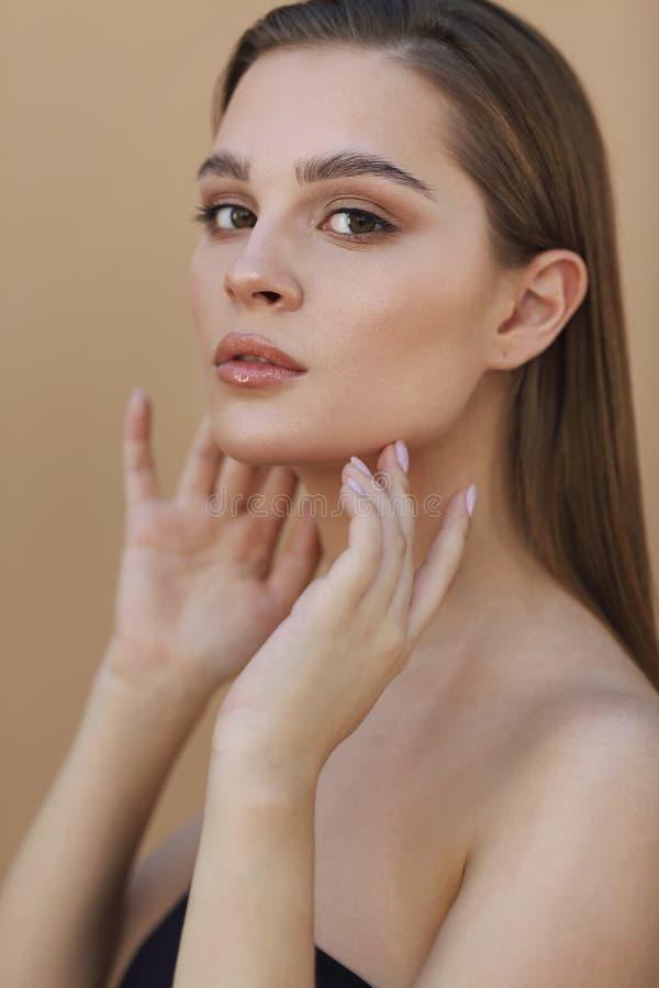Jovem mulher bonita com a pele fresca limpa que toca em própria cara Tratamento facial foto de stock royalty free