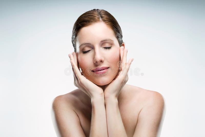 Jovem mulher bonita com pele saudável e levantamento fechado dos olhos isolada sobre o fundo branco fotografia de stock royalty free