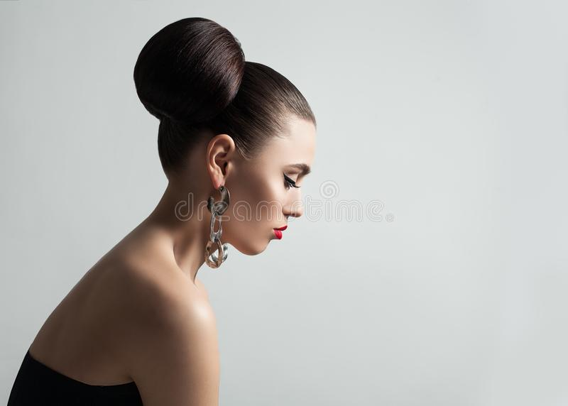A jovem mulher bonita com penteado do bolo do cabelo e o lápis de olho compõem fotografia de stock