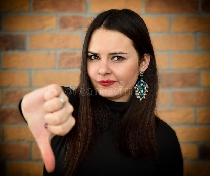 Jovem mulher bonita com polegar para baixo foto de stock