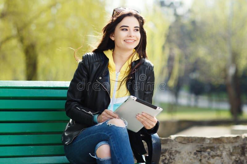 Jovem mulher bonita com sorriso bonito usando a tabuleta no parque no por do sol imagens de stock royalty free