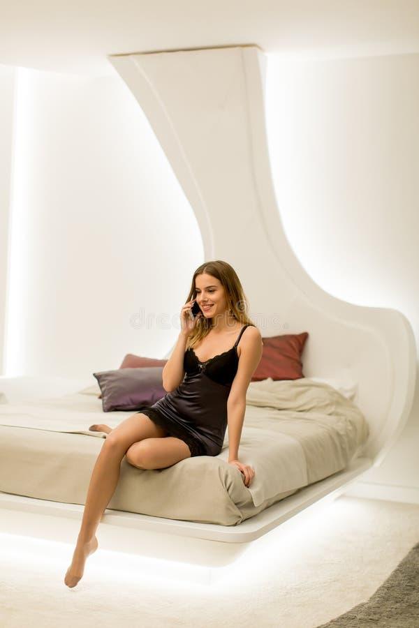 Jovem mulher bonita com telefone celular na sala moderna fotografia de stock
