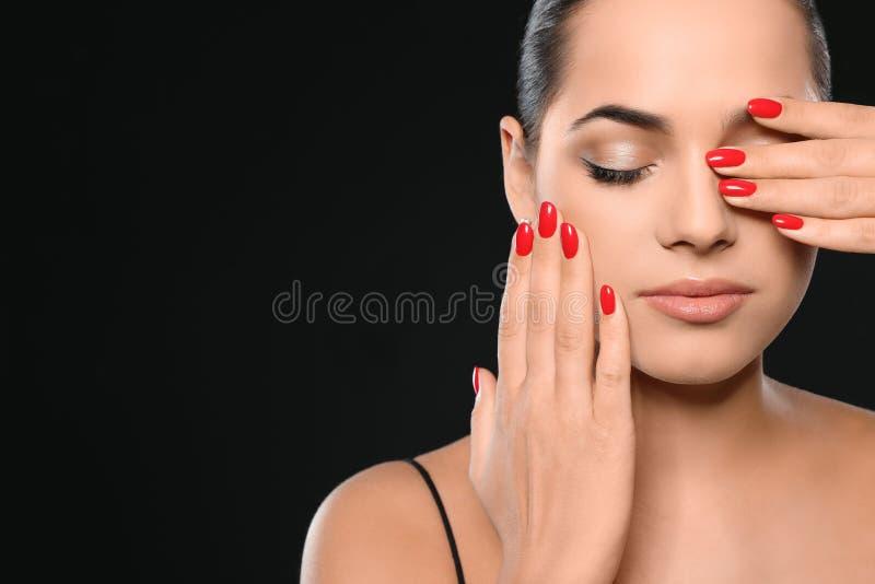 Jovem mulher bonita com tratamento de mãos brilhante no fundo preto Tend?ncias do verniz para as unhas imagens de stock