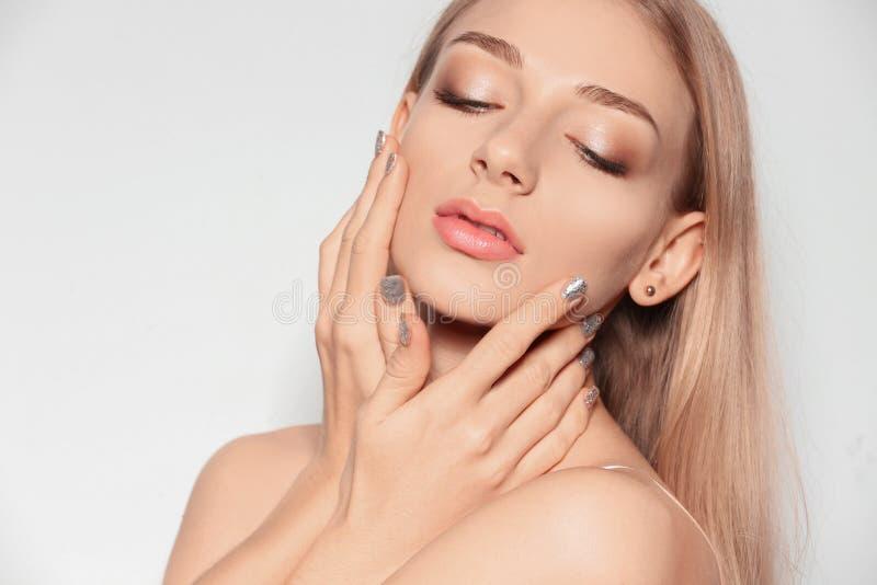 Jovem mulher bonita com tratamento de mãos brilhante Tend?ncias do verniz para as unhas fotos de stock royalty free