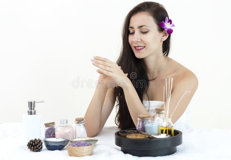 A jovem mulher bonita com tratamento esfrega o relaxamento no salão de beleza dos termas foto de stock