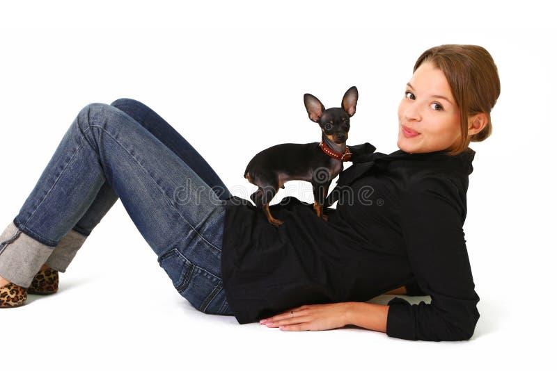 Jovem mulher bonita com um cão pequeno bonito isolado em b branco foto de stock royalty free