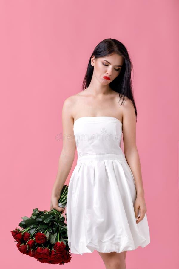 Jovem mulher bonita com um grande ramalhete de rosas vermelhas imagem de stock