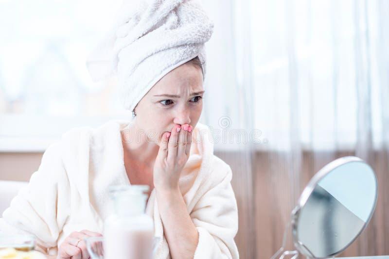 Jovem mulher bonita com uma toalha em sua cabeça que olha sua pele em um espelho Conceito da higiene e do cuidado para a pele fotografia de stock royalty free