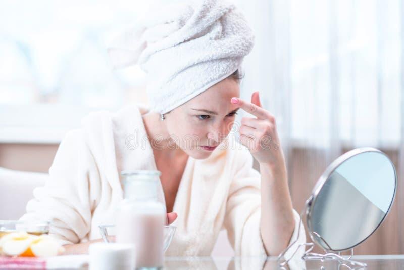 Jovem mulher bonita com uma toalha em sua cabeça que olha sua pele em um espelho Conceito da higiene e do cuidado para a pele fotos de stock