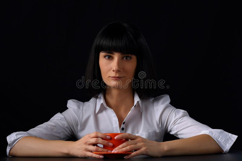 Jovem mulher bonita com uma xícara de café em um fundo escuro fotografia de stock royalty free