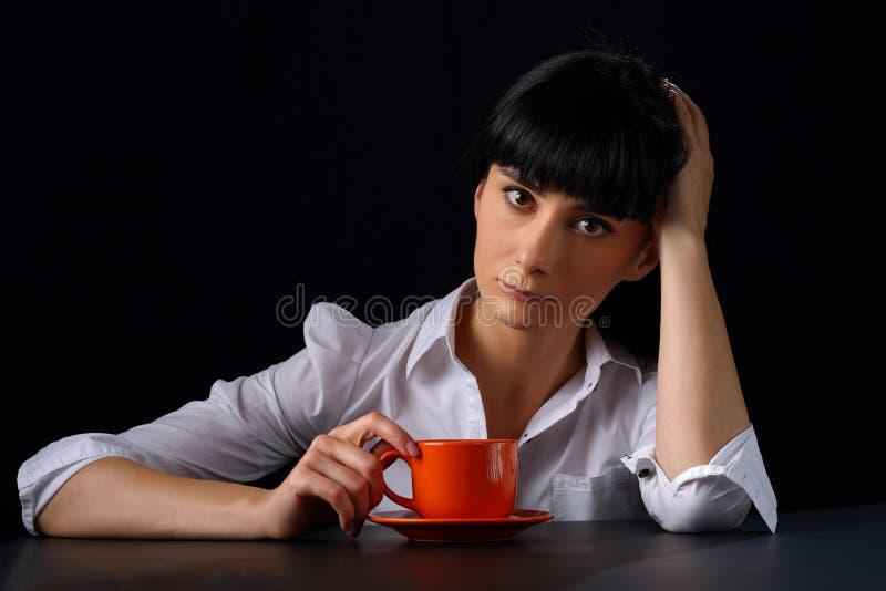 Jovem mulher bonita com uma xícara de café em um fundo escuro imagem de stock
