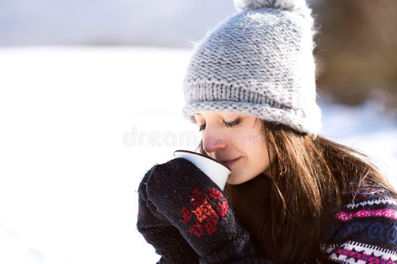 Jovem mulher bonita com a xícara de café na natureza do inverno foto de stock royalty free