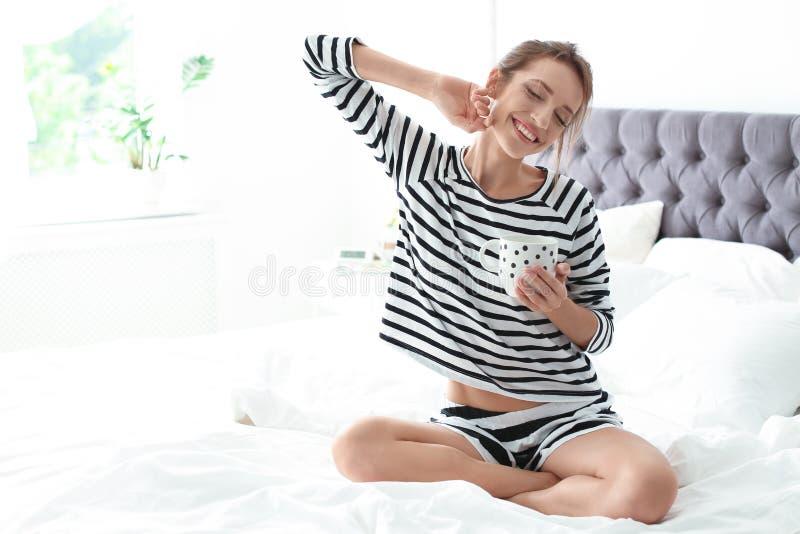 Jovem mulher bonita com a xícara de café que senta-se na cama em casa imagem de stock