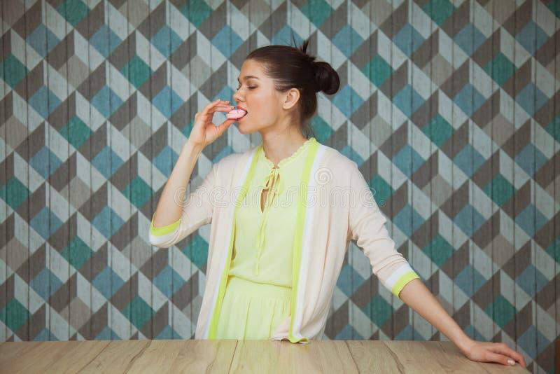 A jovem mulher bonita come a sobremesa em um fundo azul imagem de stock