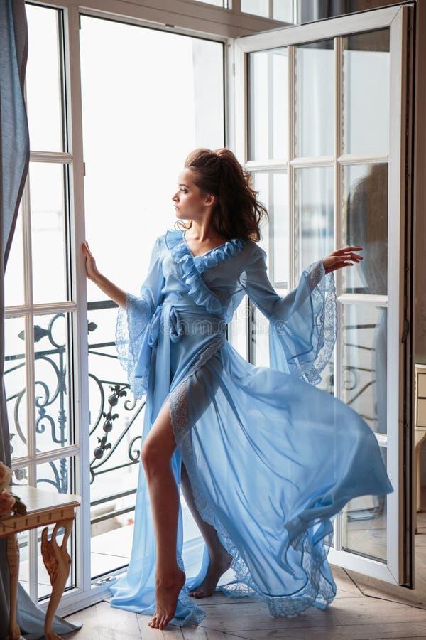 Jovem mulher bonita da noiva em um peignoir longo azul em uma manhã do casamento imagens de stock royalty free