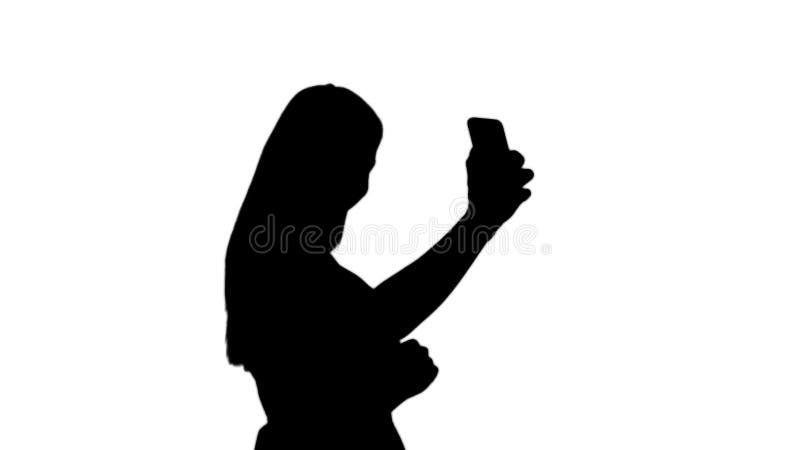 Jovem mulher bonita da silhueta que faz selfies ilustração do vetor