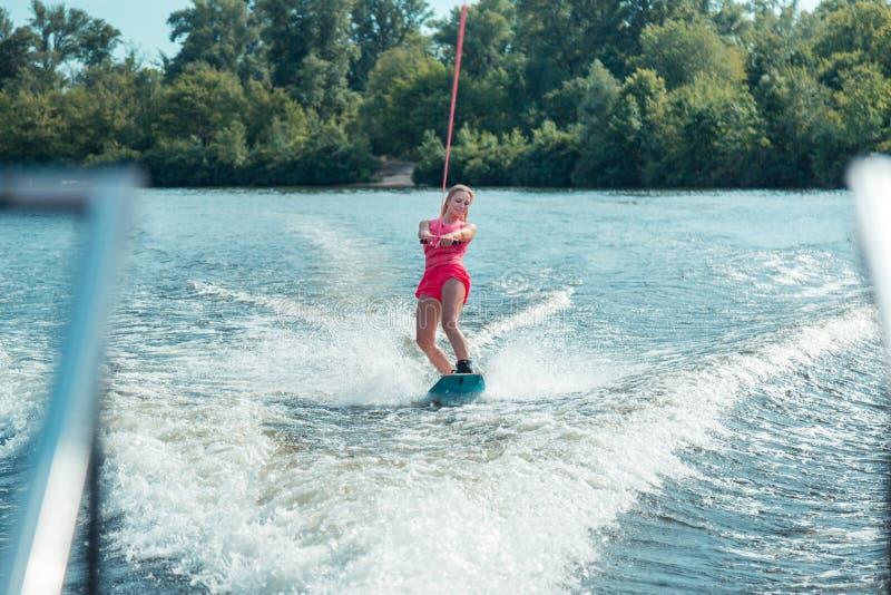 Jovem mulher bonita de cabelos compridos de sorriso que monta um wakeboard fotografia de stock royalty free