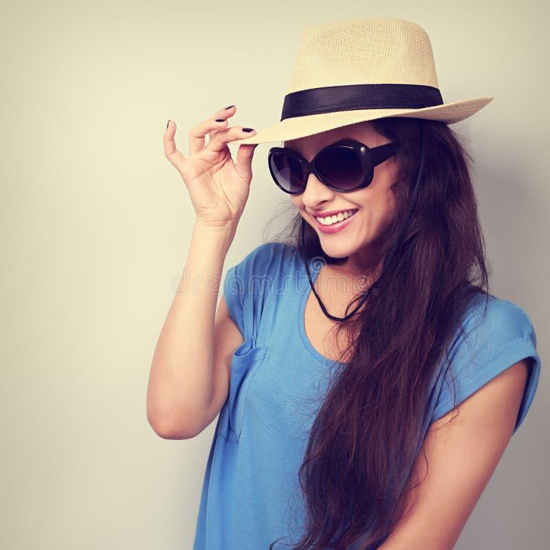 A jovem mulher bonita de sorriso com chapéu de palha e a forma expõem ao sol o gla fotografia de stock