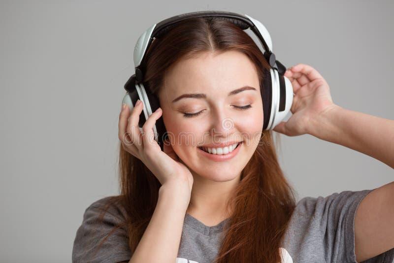 Jovem mulher bonita de sorriso que escuta a música usando fones de ouvido imagem de stock
