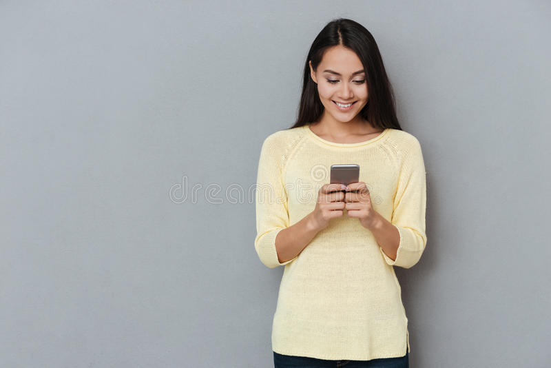Jovem mulher bonita de sorriso que está e que usa o telefone celular imagem de stock royalty free