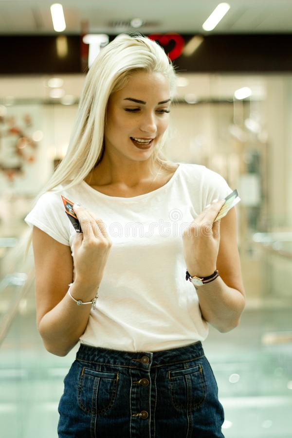 Jovem mulher bonita delgada que sorri, cartões de crédito de exame à disposição fotos de stock royalty free