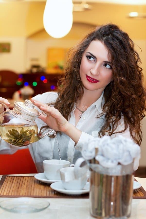 A mulher derrama o chá imagens de stock royalty free