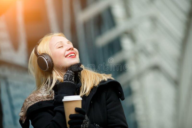 Jovem mulher bonita despreocupada que aprecia a música e o café quente fora fotografia de stock royalty free