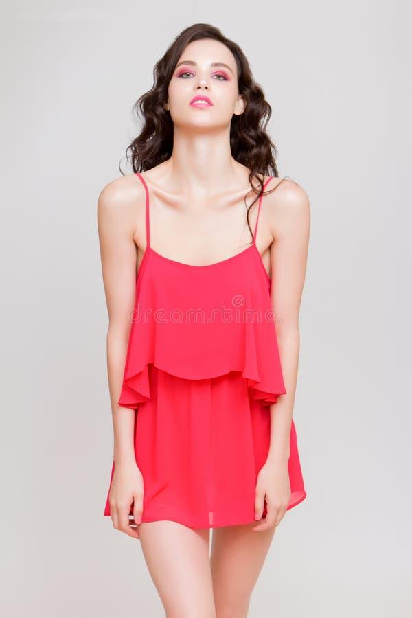 Jovem mulher bonita divertida no mini vestido cor-de-rosa que levanta no quadril e na vista imagem de stock royalty free