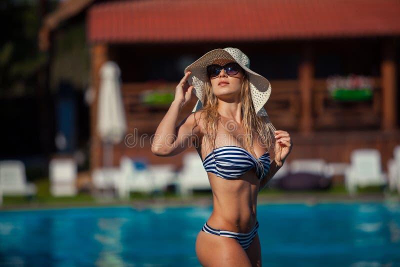 A jovem mulher bonita do summertiA bonito das férias de verão da piscina da mulher no roupa de banho na piscina está estando fotografia de stock royalty free