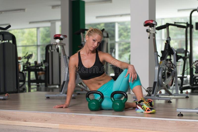 Jovem mulher bonita e atrativa com o corpo saudável que relaxa no Gym fotos de stock