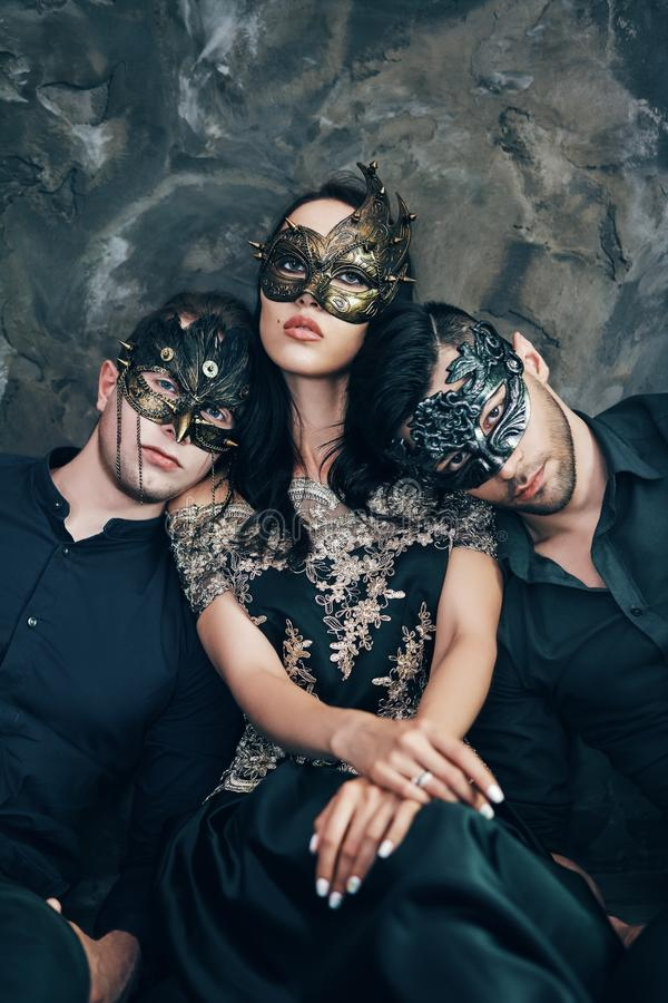 Jovem mulher bonita e dois homens na máscara preta misteriosa que senta-se no assoalho no estúdio fotos de stock