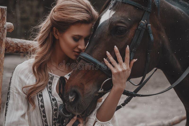 A jovem mulher bonita e romântica que veste o vestido é de abraço e de afago o cavalo no rancho fotografia de stock