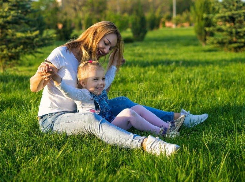 Jovem mulher bonita e seu assento pequeno da filha foto de stock royalty free