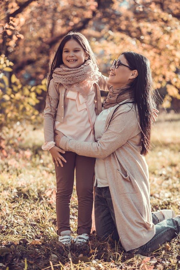 A jovem mulher bonita e sua criança no outono jardinam imagem de stock
