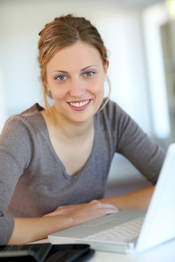 Jovem mulher bonita em casa que trabalha no portátil imagem de stock