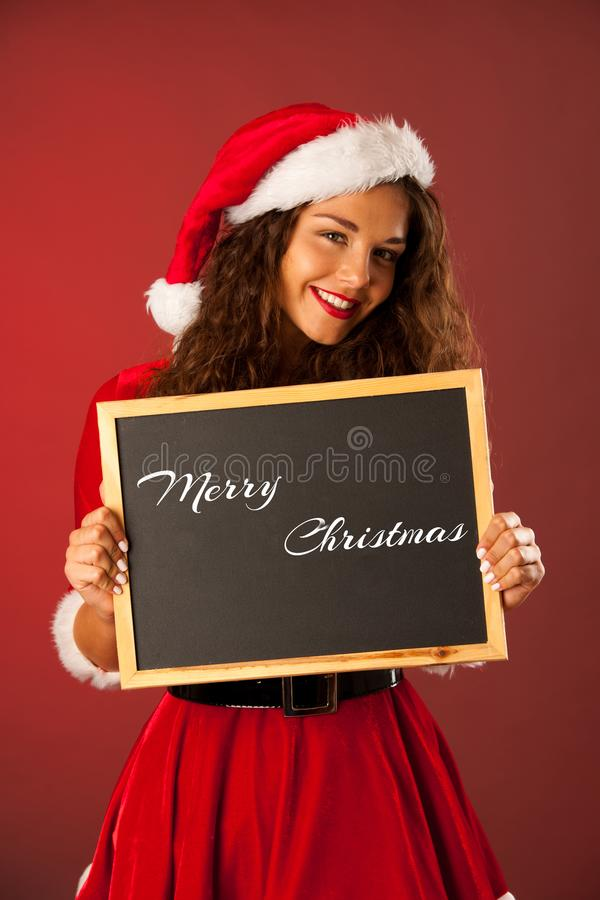 A jovem mulher bonita em dres de Santa guarda o quadro-negro sobre vagabundos vermelhos fotografia de stock royalty free